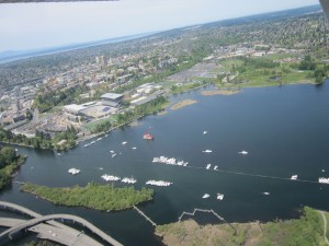 Boats lining up for front & center view of the crew races. Husky Stadium, in the midst of remodeling, is in the background
